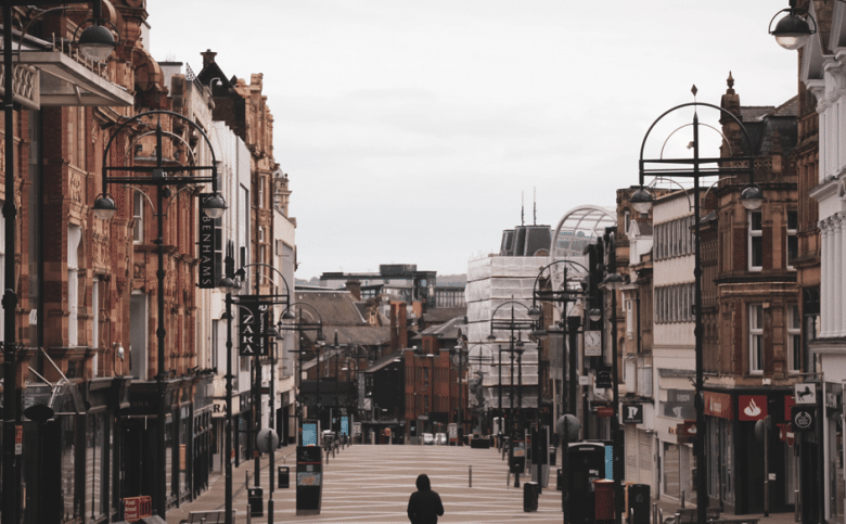 View of Briggate, Leeds with a lone, hooded figure walking away